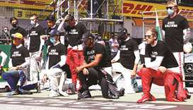 Mercedes' Lewis Hamilton, Ferrari's Sebastian Vettel and other drivers kneel on the grid wearing an