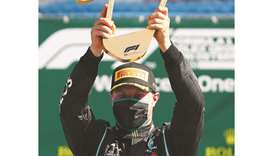 Mercedes' Finnish driver Valtteri Bottas celebrates with the trophy on the podium after winning the