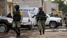 Members of the National Guard walk near the crime scene where 24 people were killed in Irapuato, Gua