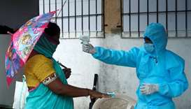 A healthcare worker checks the temperature and pulse of a resident during a check-up camp for the co