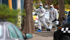 People in hazardous material overalls are seen outside of a public housing tower along Racecourse Ro