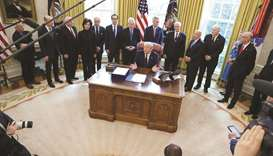 US President Donald Trump signs the $2.2tn HR 748 CARES Act coronavirus aid package bill in the Oval
