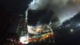 An aerial photo show firefighters trying to extinguish a massive fire that broke out in a beverage a