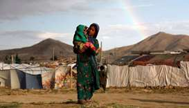 An internally displaced Afghan girl carries a child at a camp on the outskirts of Kabul.