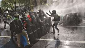 Pro-democracy protesters confront riot police whilst marching to Government House to call for the re