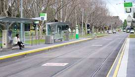 A lone passenger sits at a tram stop on a mostly-empty city centre street on the first day of a lock
