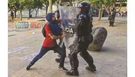 A protester clashes with a riot police officer during a rally yesterday against the government of