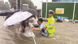 A traffic police officer guides residents to cross a flooded road with a rope during heavy rainfall