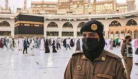 A Saudi police female officer stands guard as pilgrims perform final Tawaf during the annual Haj pil