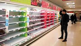 (File photo) A man stands next to shelves empty of fresh meat in a supermarket, as the number of wor