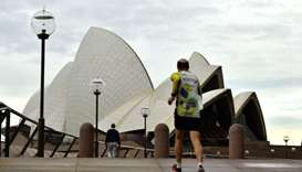 A man jogs towards the iconic Opera House in Sydney on July 23, amid a coronavirus outbreak that sta