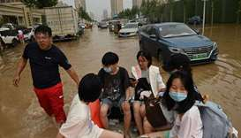 People ride on a rubber boat to cross a flooded street following heavy rain that flooded and claimed