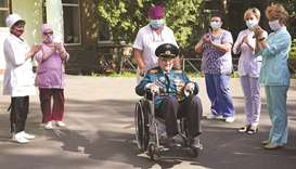 World War Two veteran Nikolay Bagayev (right) is applauded as he leaves hospital after being treated