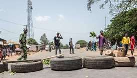 Protesters erect makeshift barricades with tires and branches during a demonstration against Benin P