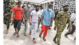 Armed Nigerian naval officers lead pirates away from a courtroom at The Federal High Court in Lagos,