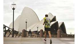 A man jogs towards the iconic Opera House in Sydney amid a coronavirus outbreak that state leaders s