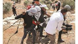 Palestinian protesters carry away an injured man during confrontations with security forces in the t