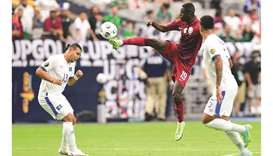 Qatar's Almoez Ali (centre) vies for the ball with El Salvador's Alexander Larin (left) during the C