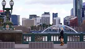 A lone woman, wearing a protective face mask, walks across an unusually quiet city centre bridge on