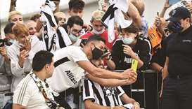 Juventus' Cristiano Ronaldo wearing a protective face mask takes a photo with fans as he arrives at