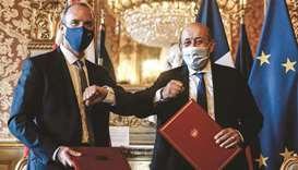 French Foreign Minister Jean-Yves Le Drian (right) elbows with Britain's Foreign Secretary Dominic R