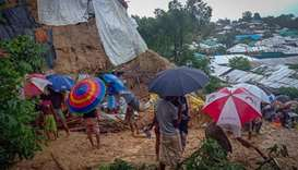 Onlookers stand as Rohingya refugees work amid the debris of houses in Balukhali camp on July 27, 20