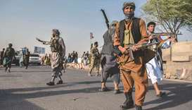 Afghan security personnel and Afghan militia fighting against Taliban stand guard in Enjil district