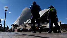 Police officers patrolling in front of the Opera House, usually packed with visitors, as a lockdown