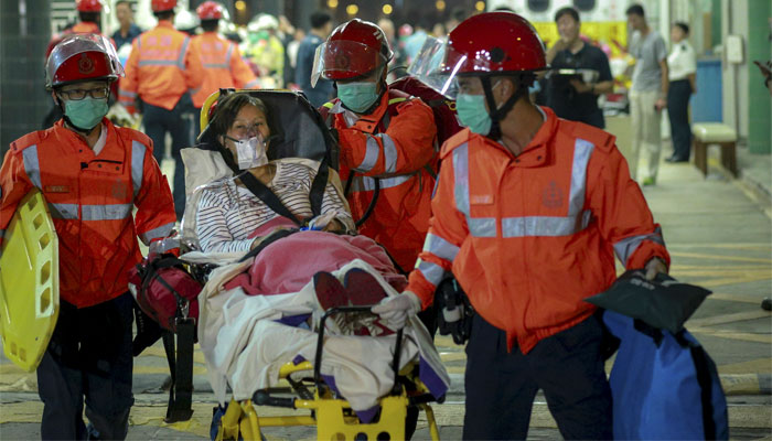 An injured ferry passenger is escorted by rescuers after getting onshore in Hong Kong. Reuters