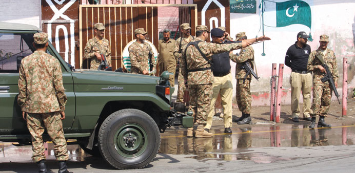 Pakistani soldiers stand guard at a polling station in Lahore.