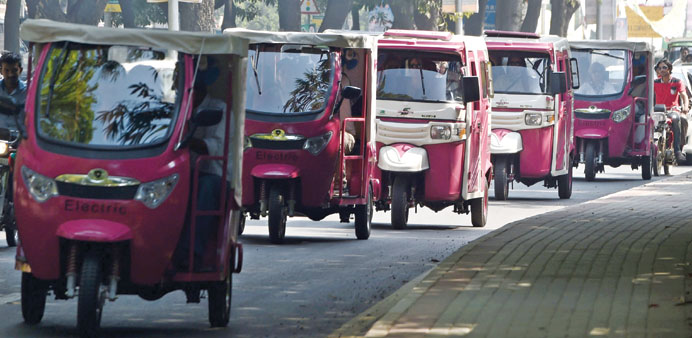 Pakistani women drive pink auto-rickshaws during a rally in Lahore yesterday.