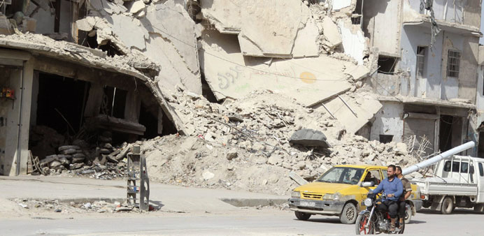 Residents drive a motorcycle in Aleppo's Al Saliheen district yesterday.