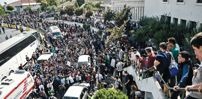 Migrants and refugees chant slogans as police block the road and bar sales of tickets to towns on th