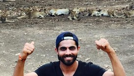 Jadeja posing in front of a pride of lions during a safari in Gir forest