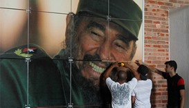 Workers install a photograph of Cuba's former president Fidel Castro in preparation for his upcoming