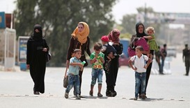 Women and children flee Hasaka after the Syrian government deployed warplanes to bomb the Kurdish-he