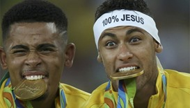 Neymar and Gabriel Jesus of Brazil bite their medals