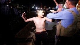 Iraqi security forces detain a boy after removing a suicide vest from him in Kirkuk, Iraq