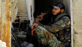 Syrian army soldiers wait at the entrance of the besieged Damascus suburb of Daraya.