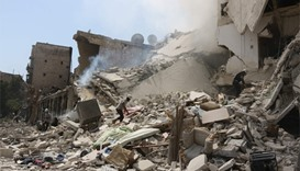 Syrian rescue workers search for victims through the rubble of a building destroyed during a reporte