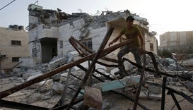 A man walks amidst debris outside the house of one of the two Palestinian gunmen