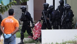 Indonesian anti-terror police carry a bag containing a suspected firearm and other evidence