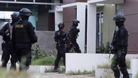 Indonesian anti-terror police are seen entering a building during a raid