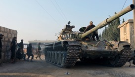Rebel fighters ride a tank in an artillery academy of Aleppo, Syria