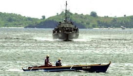 A navy cutter patrols the shores of a fishing village near the capital town of Jolo in the southern