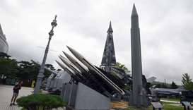 A man looks at replicas of a North Korean Scud-B missile (R) and South Korean missiles at the Korean