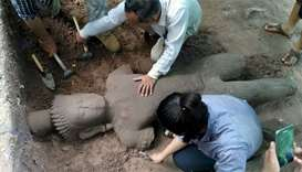 Archaeologists excavating a statue from the ground at the complex in Siem Reap province