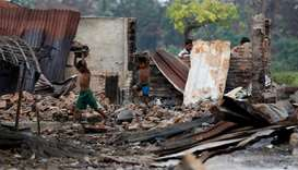 Children recycle goods from the ruins of a market which was set on fire at a Rohingya village in Rak