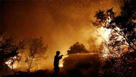 Firefighters battle wildfire near Athens, homes damaged