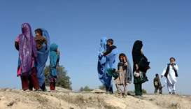 Afghan women with their children walk as they flee the area where US air forces targeted a civilian